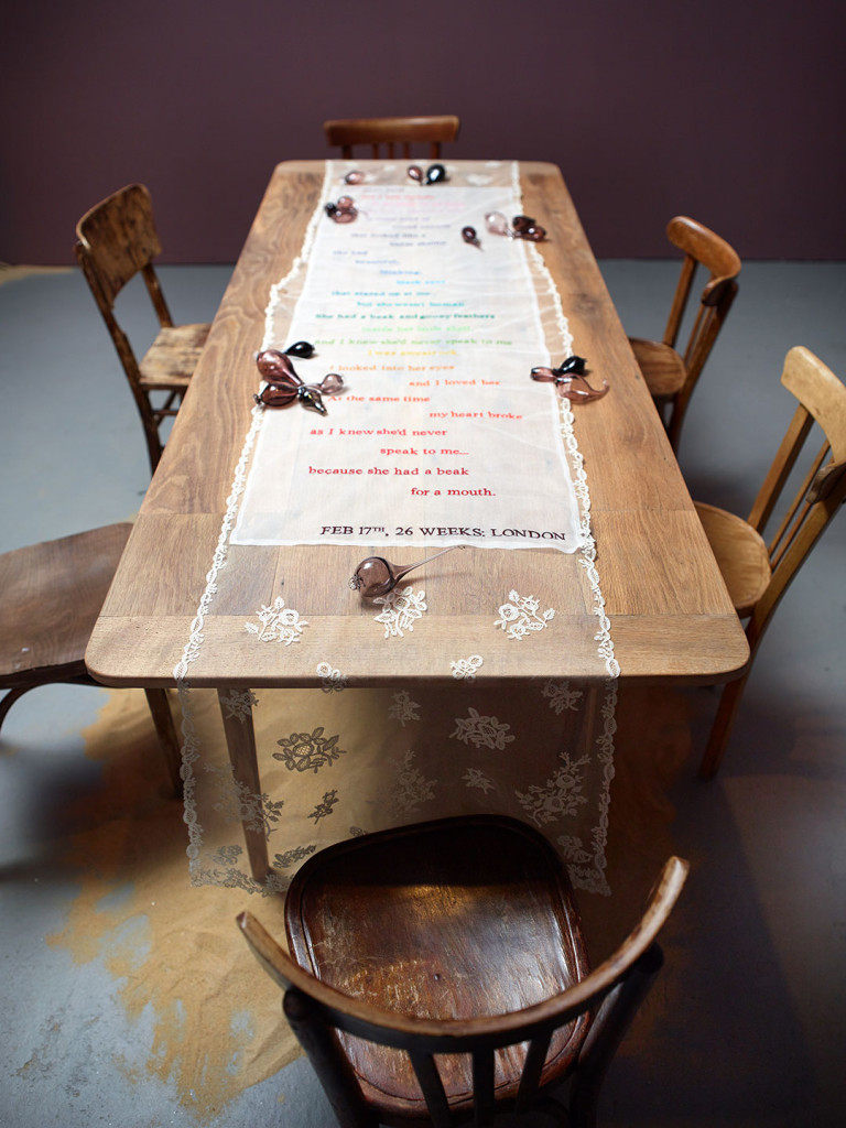Installation Art: lace colorfully embroidered with a pregnancy poem laid on top of a rustic farm table with accents of hand blown glass filled with sand.