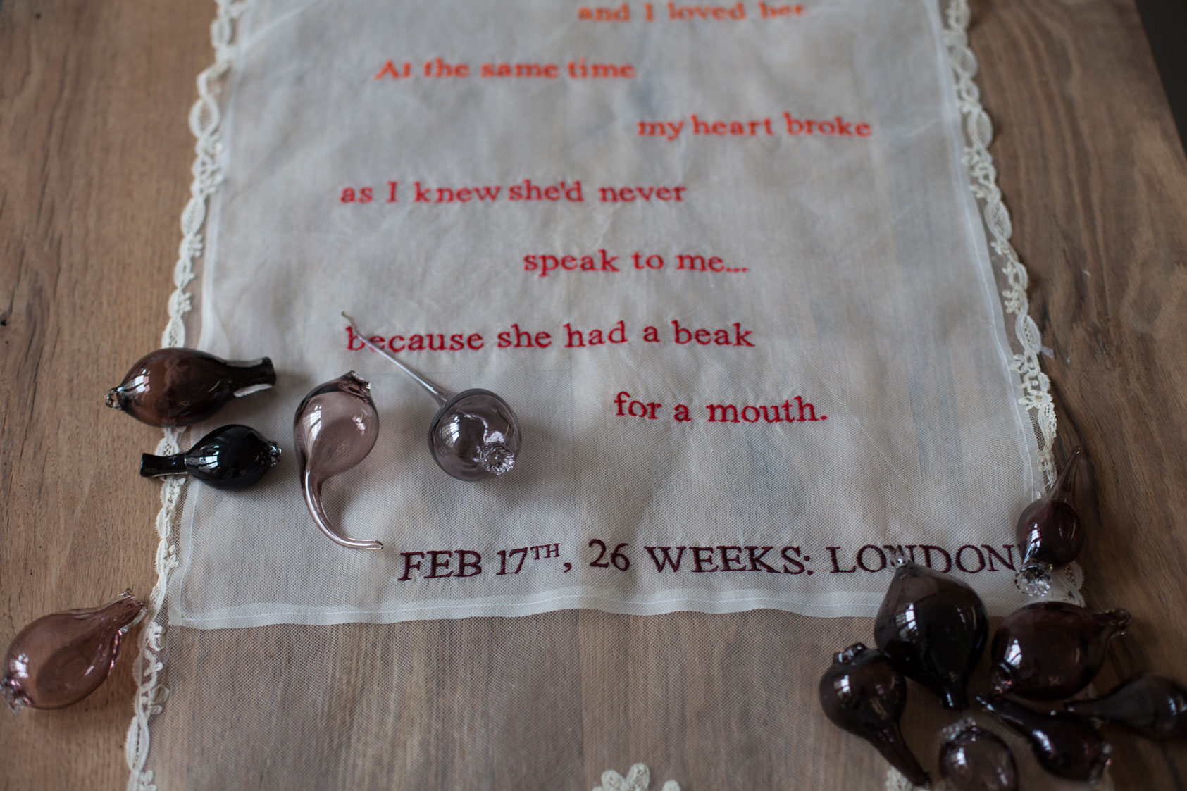 Installation art close-up of feminine lace colorfully embroidered with a poem laid on top of a rustic farm table with accents of hand blown glass filled with sand.