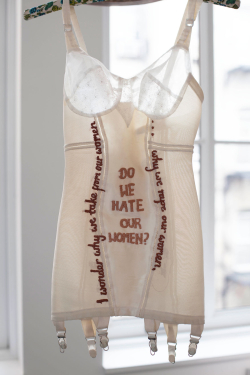"Vintage lingerie embroidered with ""do we hate our women?"" as feminist art."
