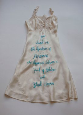 Fiber Art Piece: Vintage lingerie slip with rap definition of feminine sewn in blue.