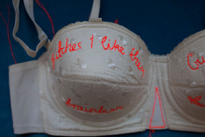 Fiber Art of rap lyrics embroidered on vintage bra.