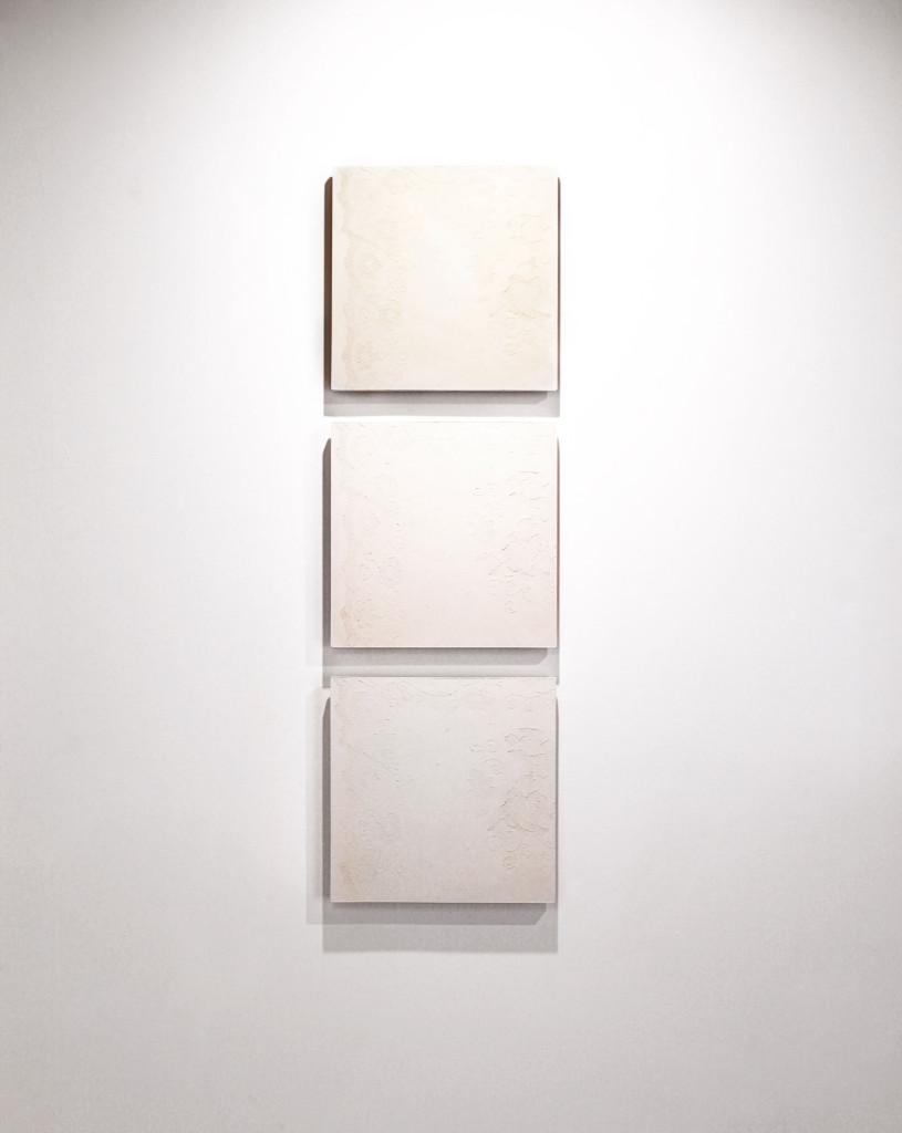 Modern wall art: feminine design shown through relief juxtaposed on concrete tile.