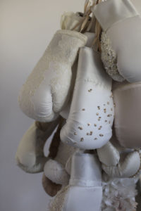Detail of large sculpture featuring boxing gloves and wedding dresses
