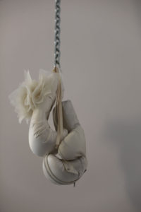 Fiber art by contemporary artist Zoe Buckman with hanging boxing gloves